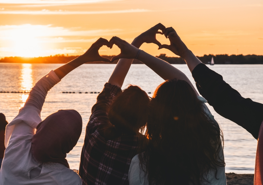 silhouette of friends looking at sunset, arms raised, making hearts with hands