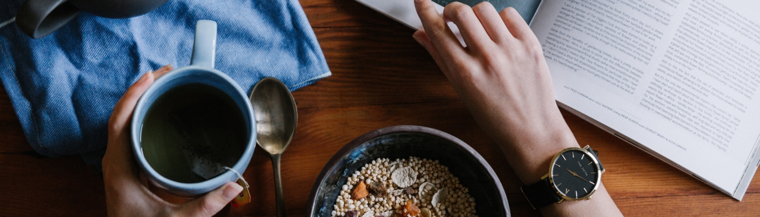left hand holding blue coffee mug right hand flipping through a magazine. A bowl of granola sits between the two hands